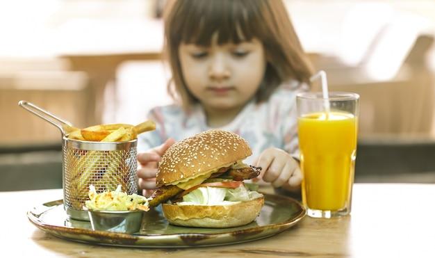 어린 소녀는 패스트 푸드 카페에서 먹는