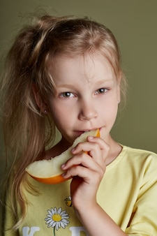 Little girl eats a melon on a green background, bright cheerful emotions