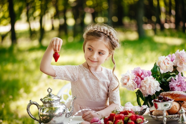 Little girl eats strawberries with tea in the park