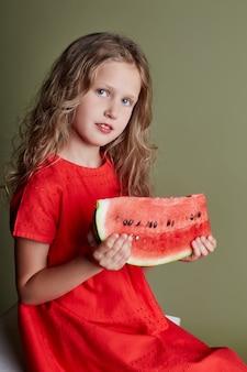 Little girl eats a watermelon in hands of teenage