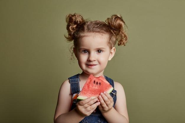 Little girl eats a watermelon