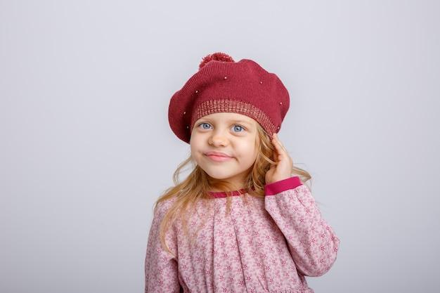 Little girl eavesdropping on grey background