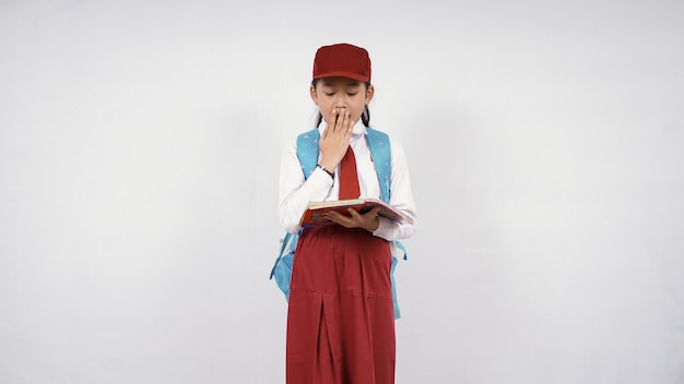 白い背景で隔離の驚きに小さな女の子の小学校の読書
