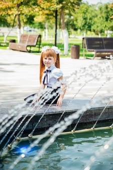 A little girl, an elementary school student, is playing merrily near the fountain .the child will refresh himself on a hot day.rest after school lessons.