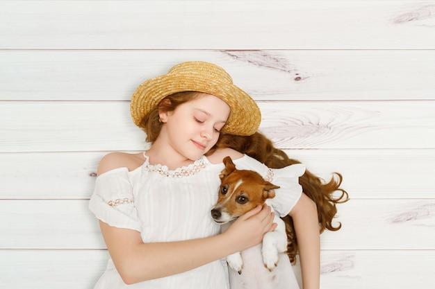 Маленькая девочка обнимает свою собаку, лежащую на деревянном полу