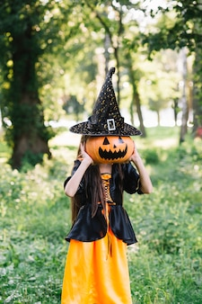 Little girl in enchantress costume closing face by pumpkin