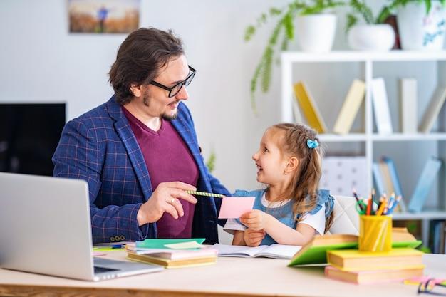 Маленькая девочка занимается уроки с учителем дома
