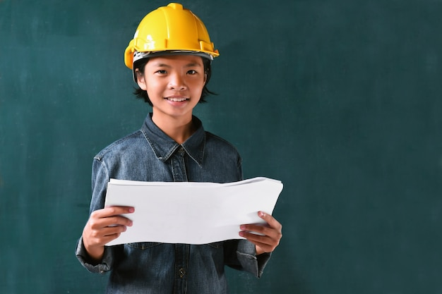 Little girl engineering helmet on board background