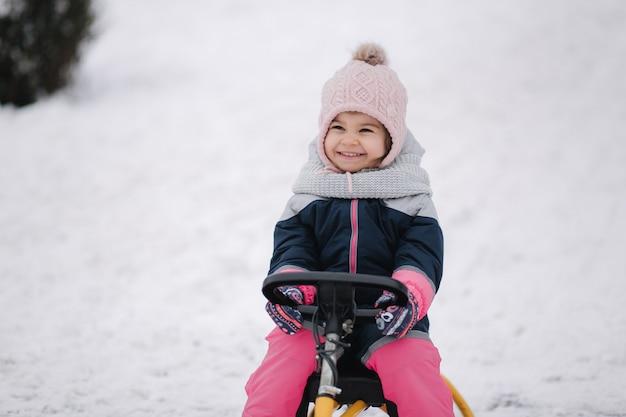 Маленькая девочка наслаждается поездкой на санях