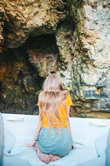小さな女の子は洞窟でボートに乗ってセーリングを楽しんでいます。