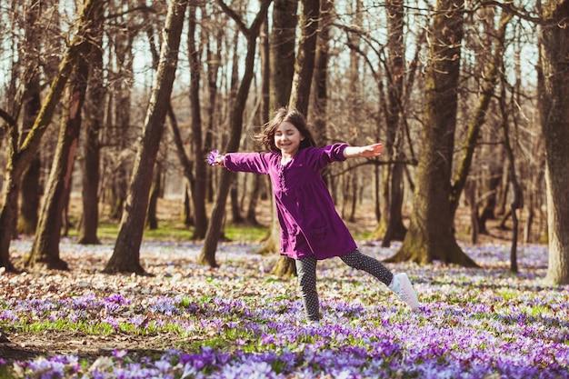 Маленькая девочка наслаждается солнцем, она мечтает и летает, вдохновленная цветущим лугом шафрана.