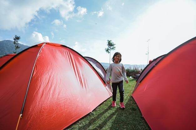 어린 소녀는 그날 정원 캠프장에서 놀고 즐겼습니다.