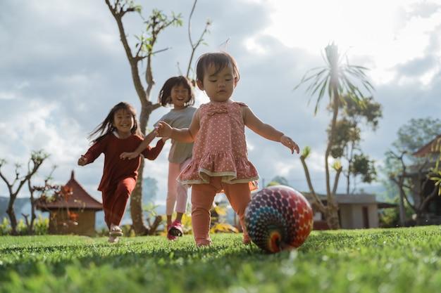 어린 소녀는 화창한 날 뒷마당에서 함께 공 놀이를 즐겼습니다.