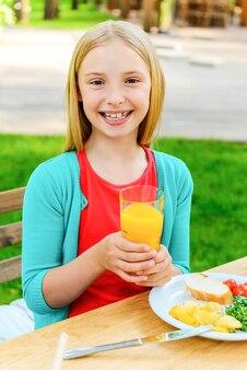 夕食を楽しんでいる少女。カメラを見て、屋外で夕食を楽しみながら笑顔の幸せな少女