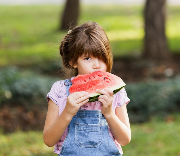 Little girl enjoying watermelon slice outside