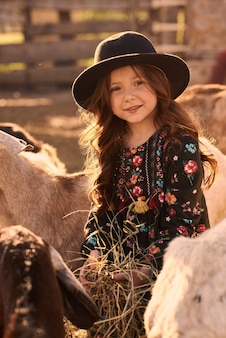 A little girl enjoys being on a farm with animals.