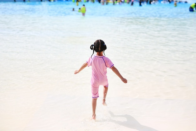 Little girl enjoys and running into big swimming pool outdoor on holidays.