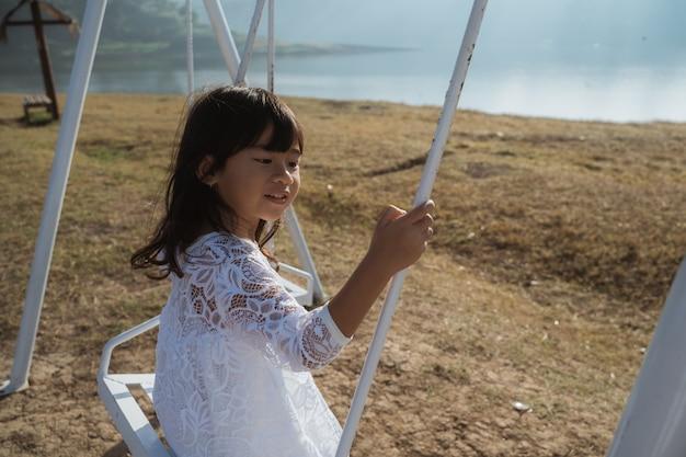 Little girl enjoys swinging alone