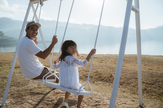 Little girl enjoys swinging with father