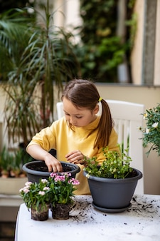 열정적으로 발코니에 냄비에 꽃을 심는 어린 소녀