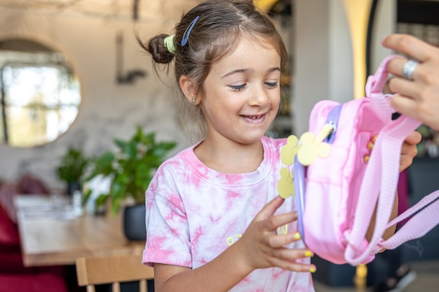 The little girl examines the backpack that was presented to her.