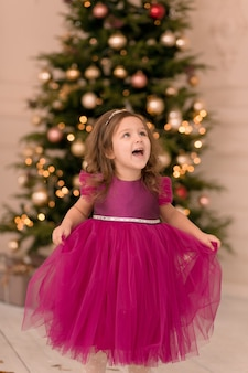 Little girl excited for christmas holidays with all these gifts and fairytale decoration.