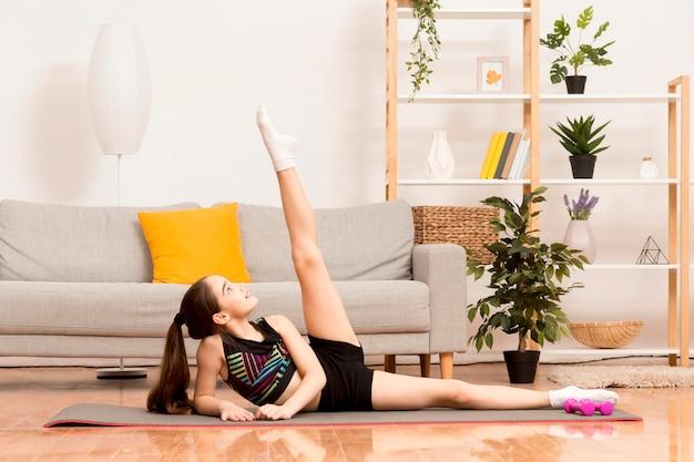 매트에 운동하는 어린 소녀
