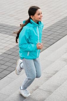 Little girl exercising on stairs