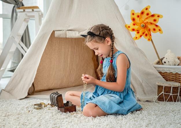 Wigwam 앞 방 바닥에 앉아 작은 가슴에서 보석을 탐험하는 어린 소녀