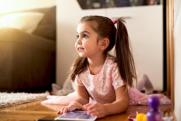 Little girl in fancy dress lying floor playing on tab