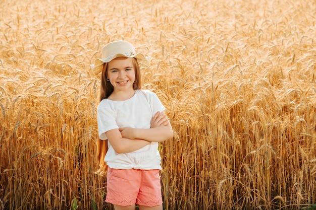 Маленькая девочка фермеров дочь в пшеничном поле смотрит в камеру и мило улыбается очаровательно ...