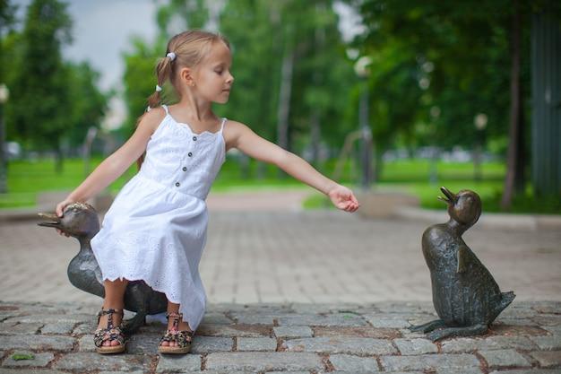 Little girl feeding the ducks figure in the park