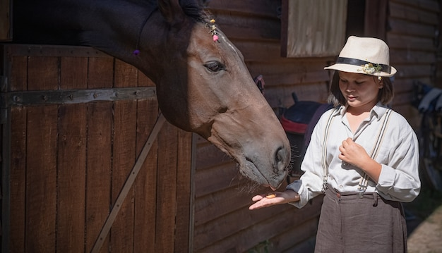 Little girl feeds thoroughbred horse. brown mare looks out from behind stable or paddock gate and delicately takes treat from palm of girl. side view.