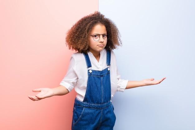 어린 소녀는 단서와 혼란을 느끼고 전혀 몰라 평평한 벽에 멍청하거나 어리석은 표정으로 당황했습니다.