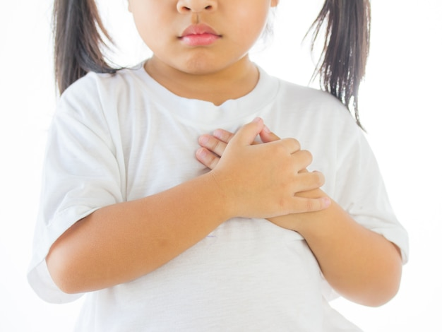 Little girl feeling heart pain and holding her chest, hand focus