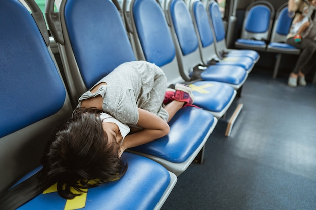 A little girl fell asleep on a bench in the bus while traveling