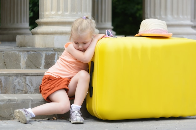 The little girl fell asleep, leaning her elbows on a big yellow suitcase.