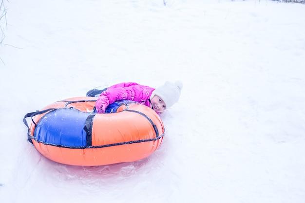 Маленькая девочка упала из надувных санок-сырников. концепция - люди и зимние виды спорта.