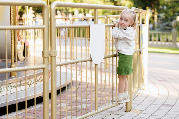 Little girl on the fence in the park in the summer