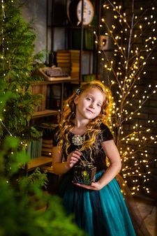 Little girl in a festive dress ans long curly hair with candle in her hands, christmas tree on background. concept of cristmas and miracles, new year decorations.
