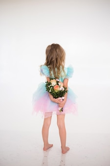 A little girl in a festive dress with a tutu skirt stands with her back and holds a bouquet of fresh flowers on a white background with a place for text