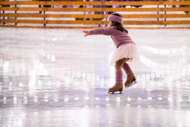 Маленькая девочка-фигуристка в розовом свитере катается зимним вечером на открытом катке, вид сзади
