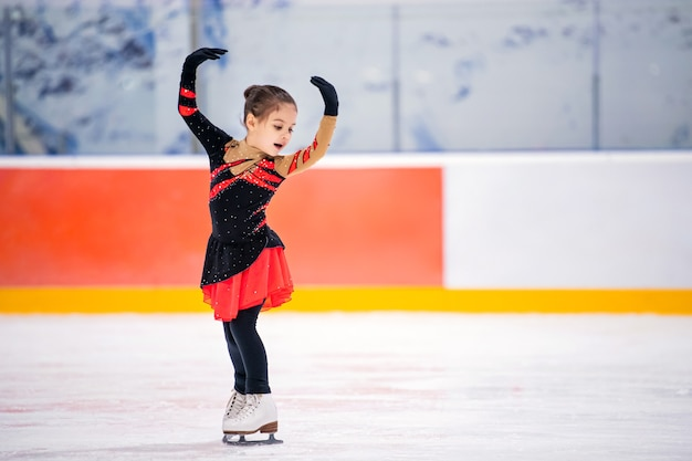 Little girl figure skater in a light pink tracksuit with a smile