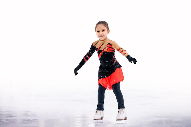 Little girl figure skater in a red black beautiful dress with a smile