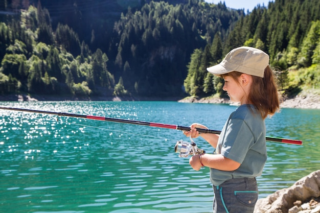 Little girl fishing in the mountains