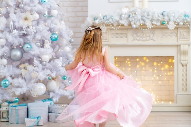 A little girl in a fluffy pink dress is spinning in the living room near the fireplace and the christmas tree, dancing developing the dress. a child in the hall with a big white christmas tree