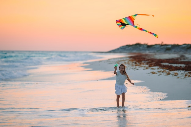 Little girl flying a kite on the beach with turquiose water