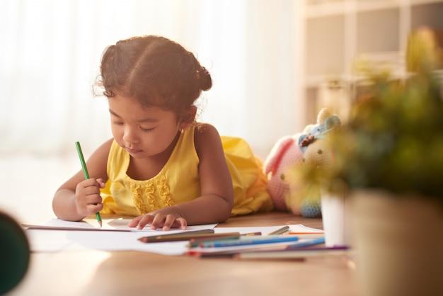 Маленькая девочка сосредоточена на рисовании