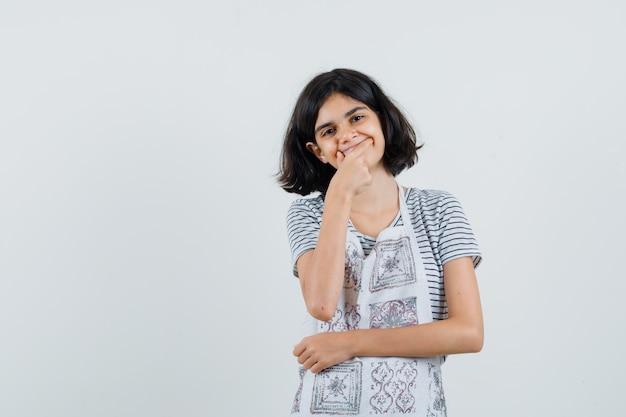 T- 셔츠, 앞치마에 얼굴에 미소를 강요하는 어린 소녀