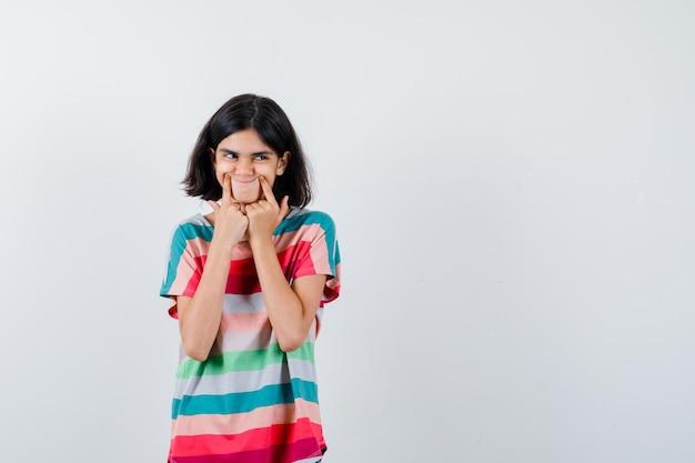Bambina costringendo un sorriso sul viso in t-shirt e guardando carino, vista frontale.